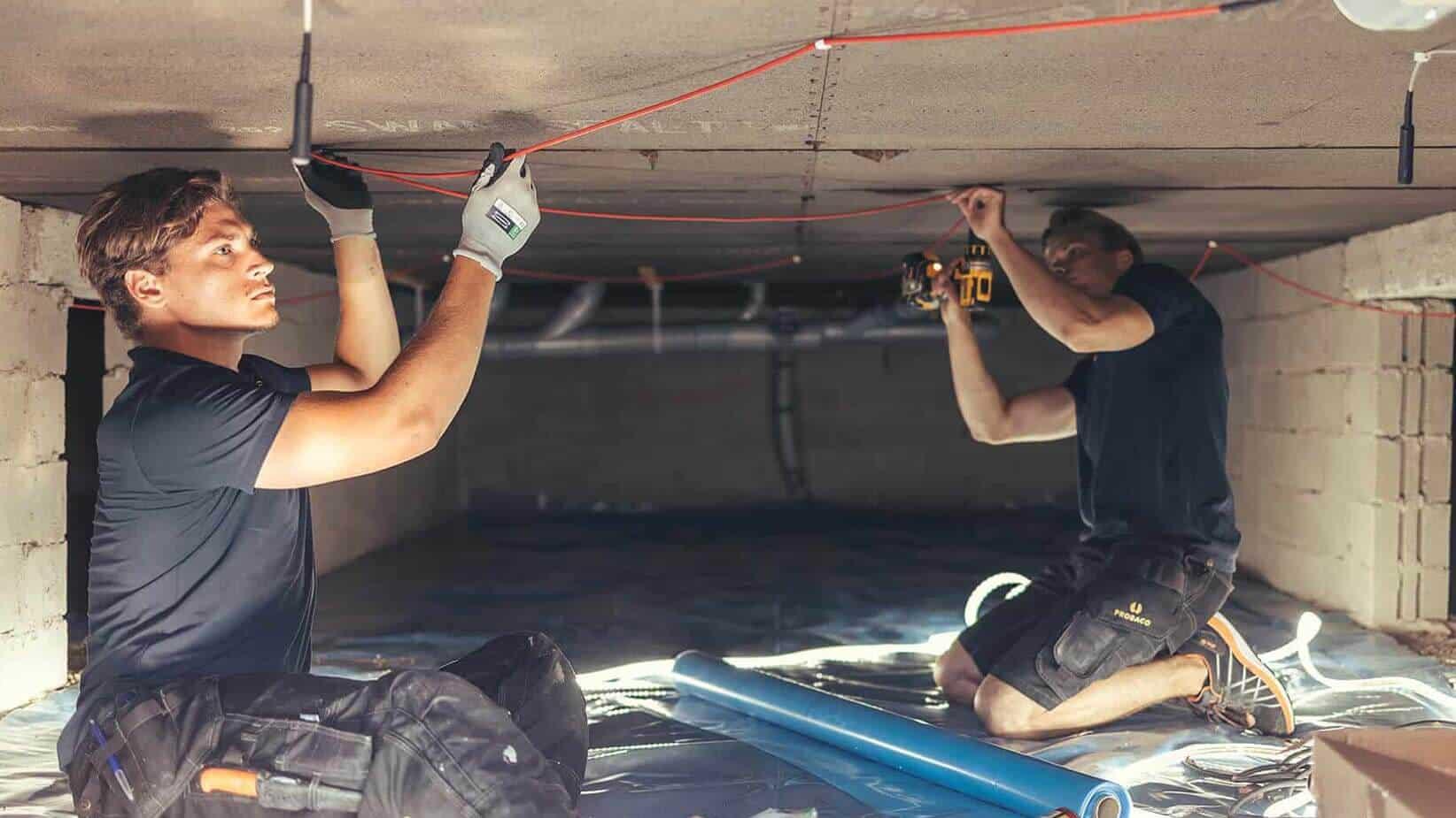 Två anställda från Probaco mäter fukt i källare